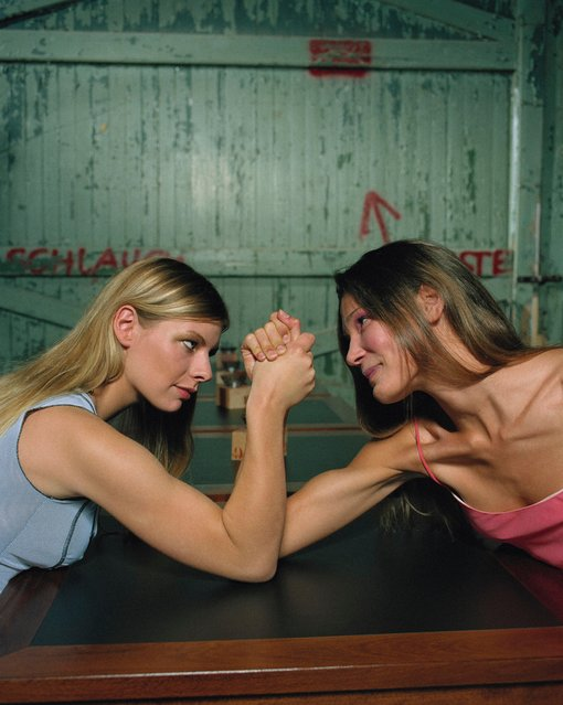 Two young women arm wrestling. (Photo by Tobbe/Getty Images)