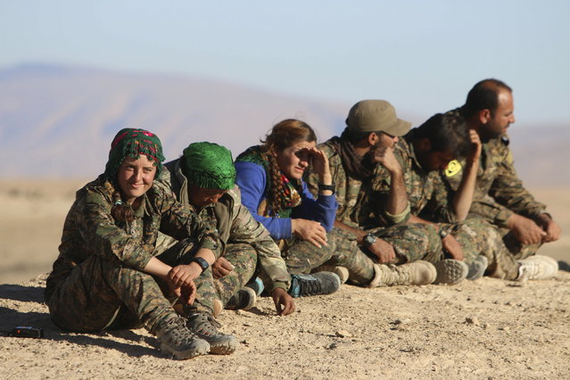 Kurdish fighters from the People's Protection Units (YPG), who are fighting alongside with the Democratic Forces of Syria, gather around the al-Khatoniyah lake area after they took control of it from Islamic State militants, near al Houl town in Hasaka province, November 14, 2015.. (Photo by Rodi Said/Reuters)