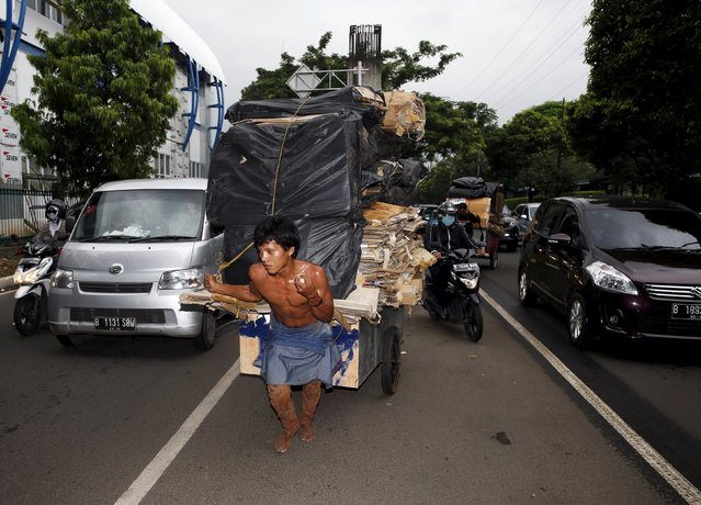 A worker drags a cart of cardboard to be recycled, on the street in Jakarta, April 13, 2015. (Photo by Reuters/Beawiharta)