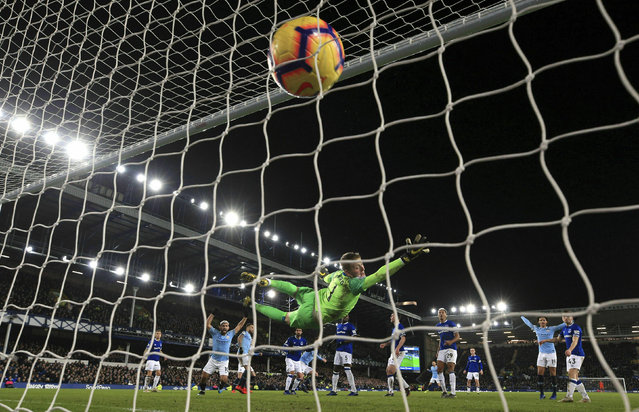 Everton goalkeeper Jordan Pickford dives in vain as Manchester City's Aymeric Laporte scores during an English Premier League soccer match at Goodison Park, Liverpool, England, Wednesday, February 6, 2019. (Photo by Peter Byrne/PA Wire via AP Photo)