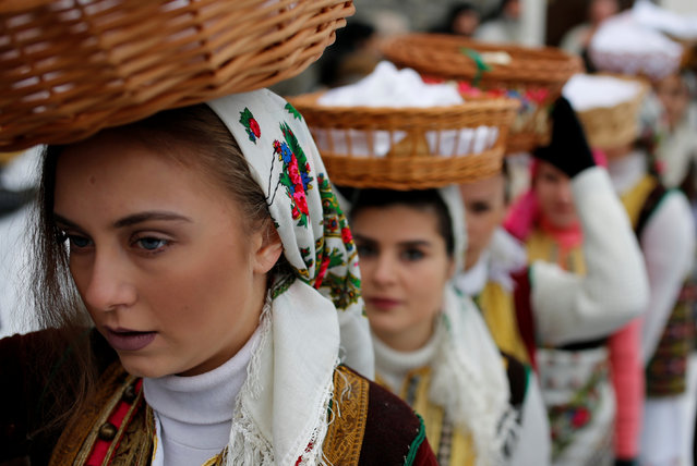 A woman dressed in a traditional folk costume balances a basket of bread on her head during Epiphany day celebration in Bitushe, Macedonia January 19, 2017. (Photo by Ognen Teofilovski/Reuters)
