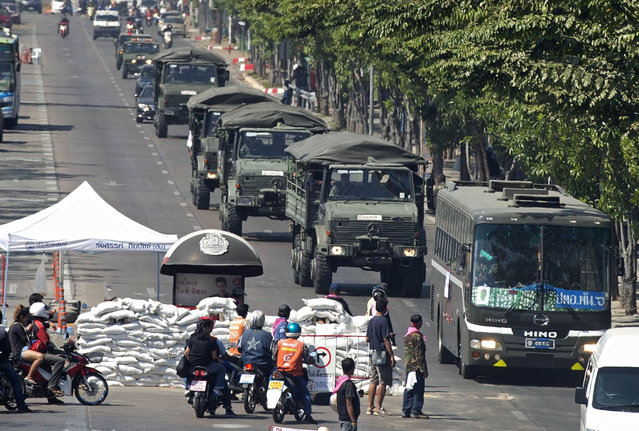 "A convoy of Thai military vehicles drive past barricades during anti-government rallies in Bangkok on January 14, 2014. Thousands of Thai opposition protesters marched on government buildings in the capital as part of their ""shutdown"" of Bangkok aimed at derailing elections and toppling the government. (Photo by Pornchai Kittiwongsakul/AFP Photo)"