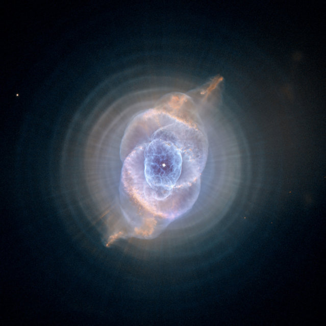 This image made by the NASA/ESA Hubble Space Telescope shows NGC 6543, the Cat's Eye Nebula. A planetary nebula forms when Sun-like stars gently eject their outer gaseous layers that form bright nebulae. In 1994, Hubble first revealed the nebula's surprisingly intricate structures, including concentric gas shells, jets of high-speed gas, and unusual shock-induced knots of gas. (Photo by NASA, ESA, HEIC, Hubble Heritage Team (STScI/AURA) via AP Photo)