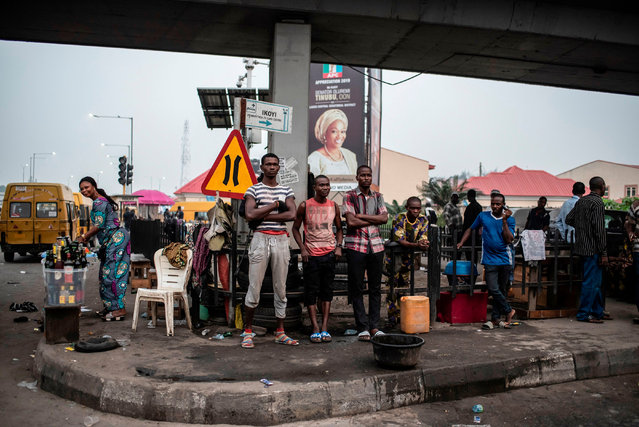 People stand at a crossroad under a bridge in Lagos on February 16, 2019 after Nigeria's electoral watchdog postponed presidential and parliamentary elections for one week, just hours before polls were due to open. The two main political parties swiftly condemned the move and accused each other of orchestrating the delay as a way of manipulating the vote. (Photo by Stefan Heunis/AFP Photo)