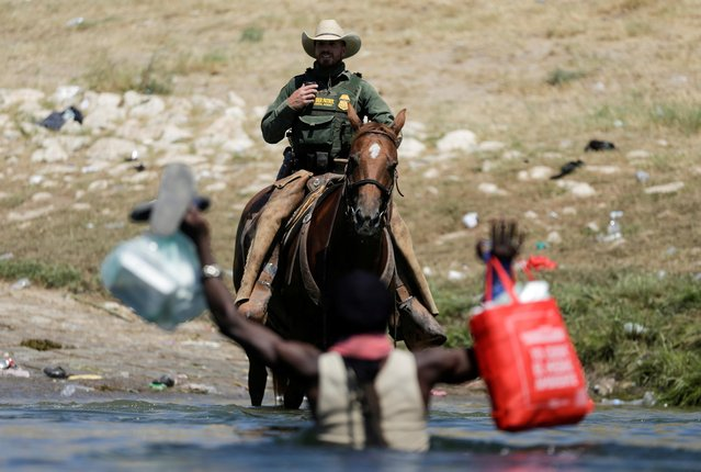 A U.S. border patrol officer cuts the way of a migrant asylum seeker as he is trying to return to the United States along the Rio Grande river, after having crossed from the United States into Mexico to buy food, as seen from Ciudad Acuna, in Ciudad Acuna, Mexico on September 19, 2021. (Photo by Daniel Becerril/Reuters)
