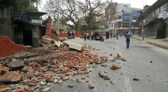 People gather in an intersection near a damaged building in Kathmandu, Nepal, Saturday, April 25, 2015. (Photo by Tashi Sherpa/AP Photo)