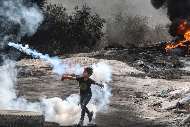 A young Palestinian boy joins fellow protesters in confrontations with Israeli security forces, following a demonstration against settlements in the West Bank village of Beita, on September 17, 2021. (Photo by Jaafar Ashtiyeh/AFP Photo)