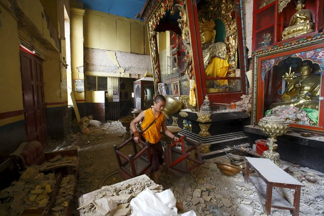 A monk carrying chairs walks out from the damaged monastery at Swoyambhunath Stupa, a UNESCO world heritage site, after Saturday's earthquake in Kathmandu, Nepal April 28, 2015. (Photo by Navesh Chitrakar/Reuters)
