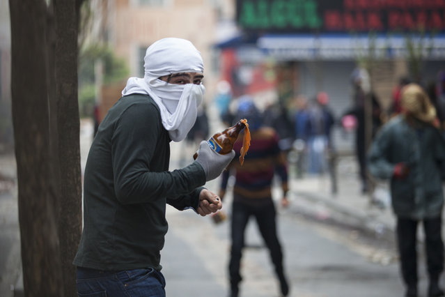 A masked protester holds a Molotov cocktail during clashes with police in Okmeydani neighbourhood in Istanbul, Turkey, May 1, 2015. (Photo by Kemal Aslan/Reuters)