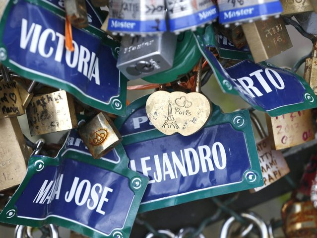 Padlocks with the Eiffel tower and mock Paris street signs models clipped by lovers are seen on the fence of the Pont des Arts over the River Seine. (Photo by Charles Platiau/Reuters)