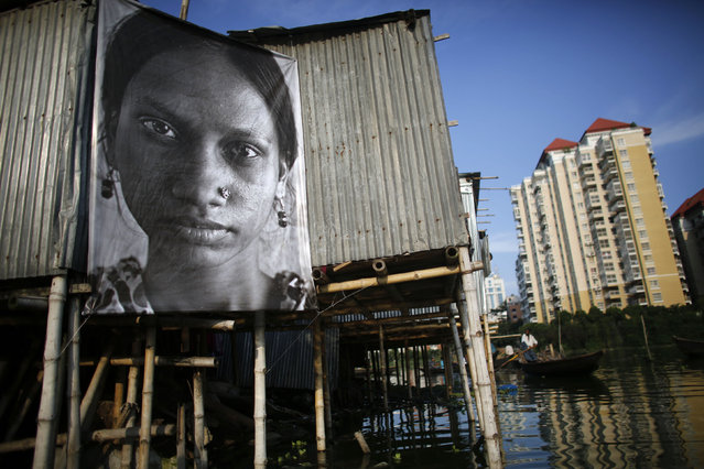A photograph of a garment worker taken by a student of the Counter Foto photography department is seen by the waterfront of Korail slum at Gulshan area in Dhaka, Bangladesh September 13, 2013. (Photo by Andrew Biraj/Reuters)