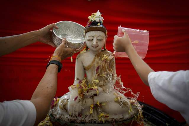 Buddhist devotees bath a Buddha statue in a ritual on Wesak Day, known as Buddha's birthday, at a temple in Petaling Jaya outside Kuala Lumpur, Malaysia on Sunday, May 3, 2015. Wesak Day, one of the holiest days for Buddhists, offers an opportunity for all followers to come together and celebrate not only Buddha's birthday, but also his enlightenment and achievement of nirvana. (Photo by Joshua Paul/AP Photo)