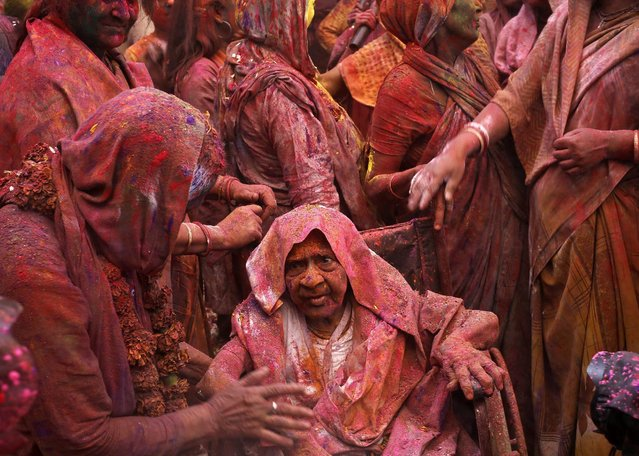 Widows daubed in colours sing religious songs as they take part in the Holi celebrations organised by non-governmental organisation Sulabh International at a temple at Vrindavan, in the northern state of Uttar Pradesh, India, March 21, 2016. (Photo by Anindito Mukherjee/Reuters)