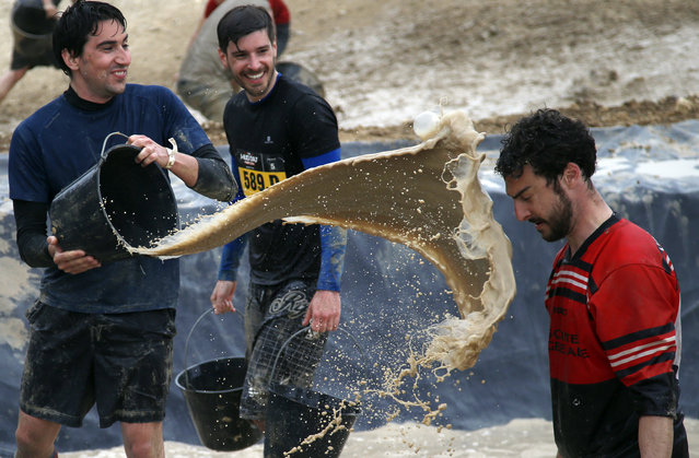 A participant in the Mud Day event throws a bucket of mud at a friend during the Mud Day run in Beynes, west of Paris, Thursday, May 8, 2014. Thousands of runners seeking a challenge competed in a circuit of approximately 13 kilometers (8 miles) with over 20 obstacles, most of them set in mud. (Photo by Francois Mori/AP Photo)