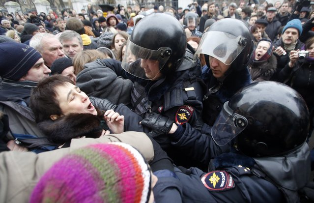 Russian police officers detain opposition activists outside a court room in Moscow, Russia, Monday, February 24, 2014, where hearings started against opposition activists detained on May 6, 2012 during a rally at Bolotnaya Square. (Photo by Denis Tyrin/AP Photo)