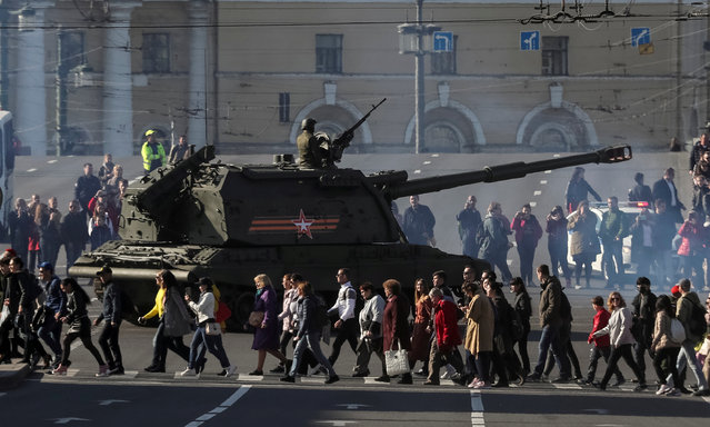 Pedestrians cross a road nest to a self-propelled howitzer during a rehearsals for the Victory Day military parade in Saint Petersburg, Russia on April 30, 2019. (Photo by Anton Vaganov/Reuters)
