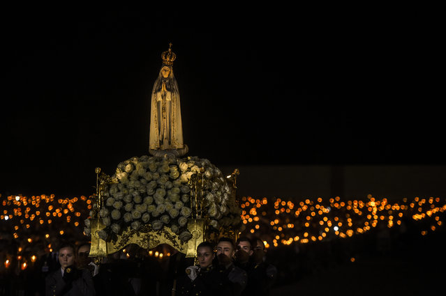 A statue of Our Lady Fatima is carried during the candle procession at the Fatima shrine in Fatima, central Portugal, on May 12, 2019. Thousands of pilgrims converged on the Fatima Sanctuary to celebrate the anniversary of Fatima's miracle when three shepherd children claimed to have seen the Virgin Mary in May 1917. (Photo by Patricia De Melo Moreira/AFP Photo)