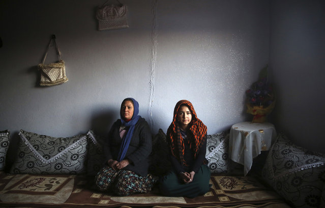 Tahsiye Ozyilmaz, 33, and her daughter Halime, 14, pose for a photograph at their home in Zeytinpinar Village of Derik, a Kurdish town in Mardin Province February 1, 2014. Tahsiye, who is a housewife, didn't go to school. She says would have liked to become a teacher, but she had an arranged marriage at the age of 17. She wants her daughter to finish her education, and would like her to be a doctor. Halime stopped going to school last year because it was 10 km (6 miles) from her house and the journey was too difficult. (Photo by Umit Bektas/Reuters)