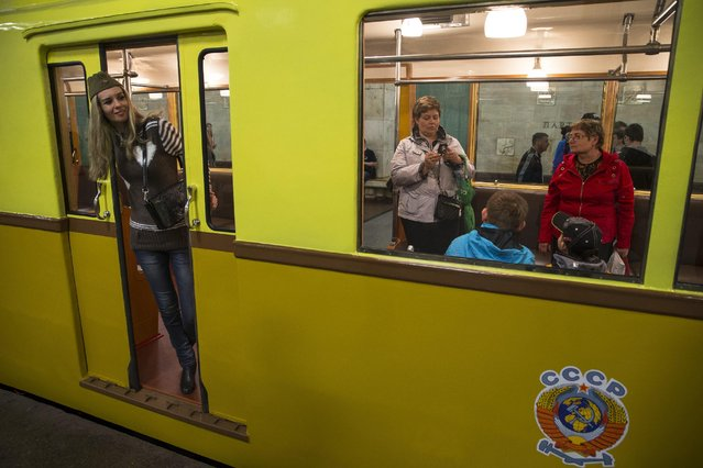People make pictures in a Soviet-era vintage subway car, with a Soviet railways emblem on the side of it, parked in the Partizanskaya subway station in Moscow, Russia, Friday, May 15, 2015. (Photo by Pavel Golovkin/AP Photo)