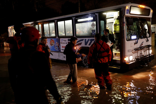 A man walks towards an awaiting evacuation bus after rescue crews evacuated a developmental home as heavy rains overflowed nearby Coyote Creek in San Jose, California, U.S. February 21, 2017. (Photo by Stephen Lam/Reuters)