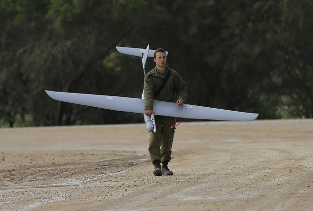 An Israeli soldier carries a drone near the Israel and Gaza border on Thursday, March 13, 2014. Gaza militants resumed rocket fire toward Israel on Thursday, striking the outskirts of two major cities a day after launching the largest barrage since an eight-day Israeli offensive in late 2012. Israel has responded with a series of airstrikes on militant targets. (Photo by Tsafrir Abayov/AP Photo)