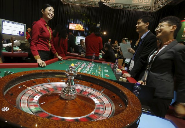 """Kathryn Lagrata (L), 25, from Solaire Resort and Casino in Manila, Philippines, chats with judges as she takes part in an """"All Asia Dealers Championship"""" at the Global Gaming Expo (G2E) Asia in Macau, China May 19, 2015. (Photo by Bobby Yip/Reuters)"""
