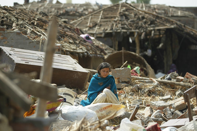 A woman sits in the middle of the debris of a residential house damaged in rainstorm in Bara district, 125 kilometers (75 miles) south of Kathmandu, Nepal, Monday, April 1, 2019. Rescuers struggled Monday to reach villages in southern Nepal cut off by a powerful rainstorm that killed at least 28 people and injured hundreds more. (Photo by Niranjan Shrestha/AP Photo)