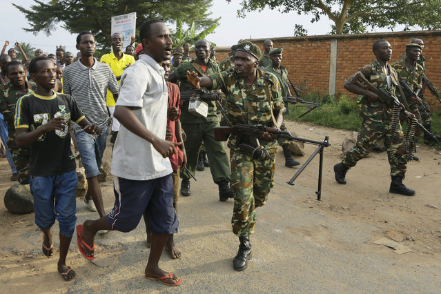 Soldiers attempt to stop a group of demonstrators running towards a cordon of police in the Musaga neighborhood of Bujumbura, Burundi, Wednesday May 20, 2015. (Photo by Jerome Delay/AP Photo)