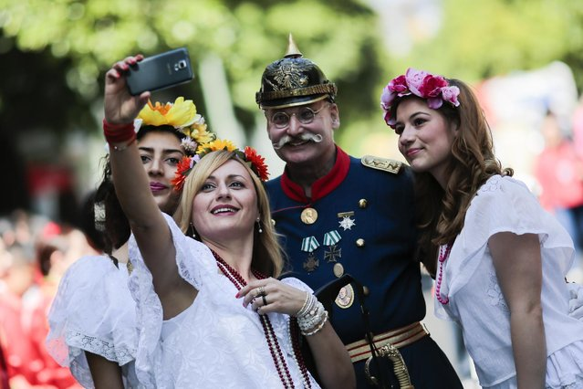 Participants of the annual Carnival of Cultures parade take a selfie   prior to the parade in Berlin, Germany, Sunday, May 24, 2015. (Photo by Markus Schreiber/AP Photo)