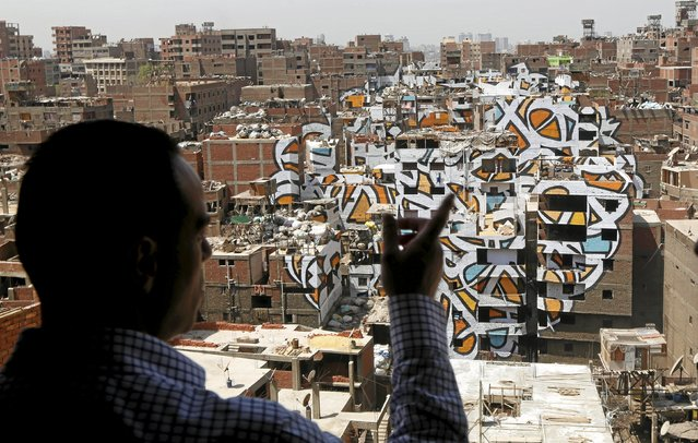 "A man looks at a mural painted on the walls of houses in Zaraeeb, created by French-Tunisian artist El Seed, in the shanty area known also as Zabaleen or ""Garbage City"" on the Mokattam Hills in eastern Cairo, Egypt, April 4, 2016. (Photo by Amr Abdallah Dalsh/Reuters)"