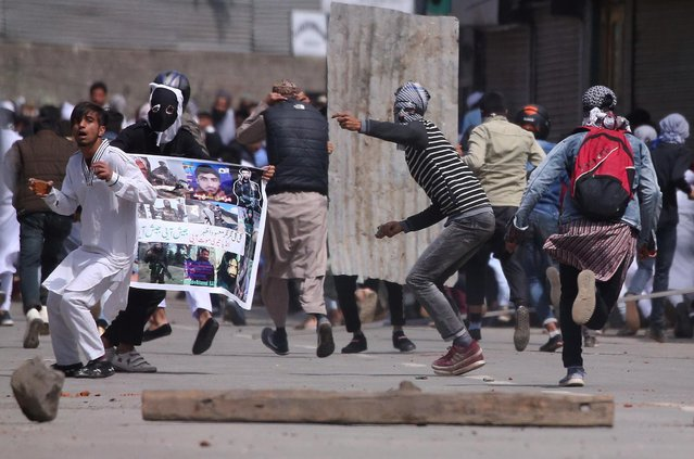 Demonstrators throw stones towards Indian police during clashes after the Eid al-Fitr prayers in Srinagar, June 5, 2019. (Photo by Danish Ismail/Reuters)