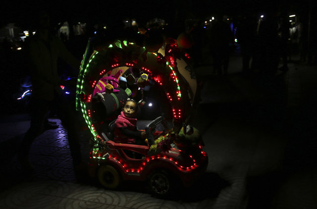 A Palestinian child rides an electronic toy car while touring at the Unknown Soldier square in Gaza City, Thursday, April 14, 2016. (Photo by Adel Hana/AP Photo)
