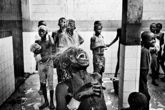 Street children bathe at a care center in Kinshasa, Democratic Republic of Congo, in 2005. Some facilities are available in exchange for light labor. These consist of very basic schooling, food and lodgings. (Photo by Marcus Bleasdale/VII Photo Agency)