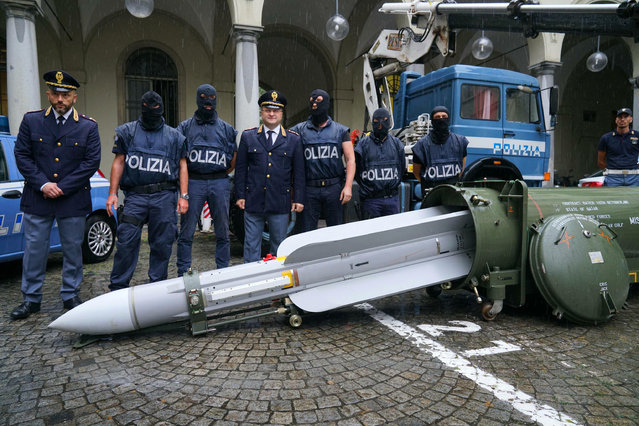 Police stand by a missile seized at an airport hangar near Pavia, northern Italy, following an investigation into Italians who took part in the Russian-backed insurgency in eastern Ukraine, in Turin, Italy, Monday, July 15, 2019. Police in northern Italy have detained three men, including one tied to a neo-fascist Italian political party, after uncovering a huge stash of automatic weapons, a missile and Nazi propaganda. (Photo by Tino Romano/ANSA via AP Photo)