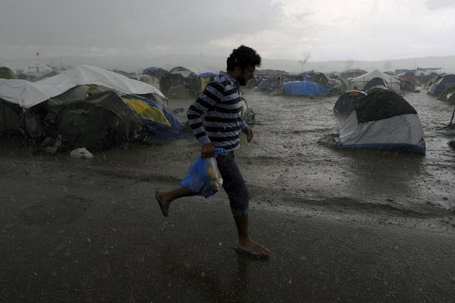A refugee runs under heavy rainfall at a makeshift camp for migrants and refugees at the Greek-Macedonian border near the village of Idomeni, Greece, April 24, 2016. (Photo by Alexandros Avramidis/Reuters)