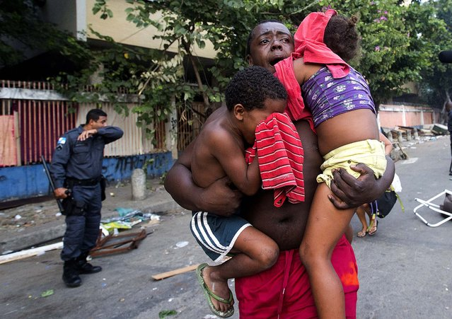 A man runs while he carries two children during an eviction in Rio de Janeiro, on April 11, 2014. Squatters in Rio de Janeiro are clashing with police after a Brazilian court ordered that 5,000 people be evicted from abandoned buildings of a telecommunications company. Officers have used tear gas and stun grenades to try to disperse the families. (Photo by Silvia Izquierdo/Associated Press)