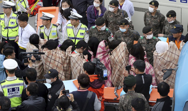 Rescued passengers from a ferry sinking off South Korea's southern coast, are escorted by rescue teams on their arrival at a port in Jindo, south of Seoul, South Korea, Wednesday, April 16, 2014. (Photo by Park Chul-heung/Reuters/Yonhap)