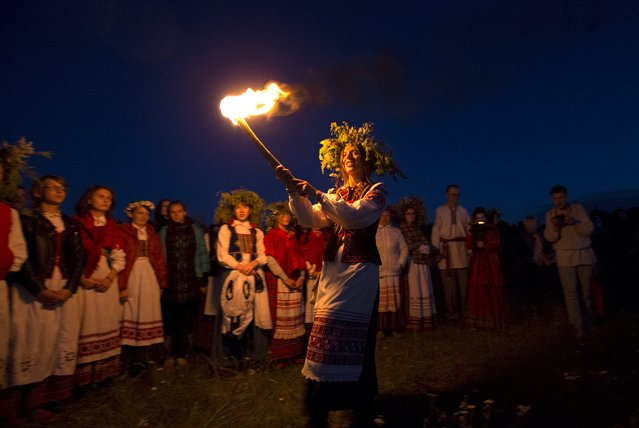 Belarusian people take part in the Ivan Kupala festival near the town of Rakov, west of Minsk June 27, 2015. The ancient tradition, originating from pagan times, is usually marked with grand overnight festivities. On Kupala night, people sing and dance around campfires, believing it will purge them of their sins and make them healthier. (Photo by Vasily Fedosenko/Reuters)