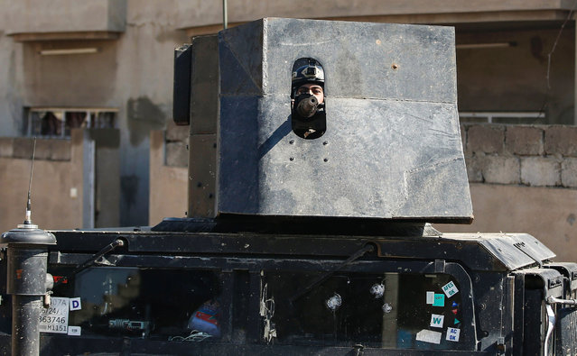 A member of the Iraqi forces mans a turret mounted atop a humvee as troops advance towards the Old City in western Mosul on March 24, 2017, during an offensive to retake the city from Islamic State (IS) group fighters. (Photo by Ahmad Gharabli/AFP Photo)