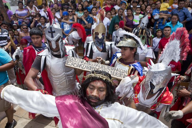 """Actors playing the part of Jesus and a Roman soldiers participate in """"Los Encadenados"""", or The Chained Ones procession on Good Friday during Holy Week in Masatepe, Nicaragua, Friday, April 18, 2014. (Photo by Esteban Felix/AP Photo)"""