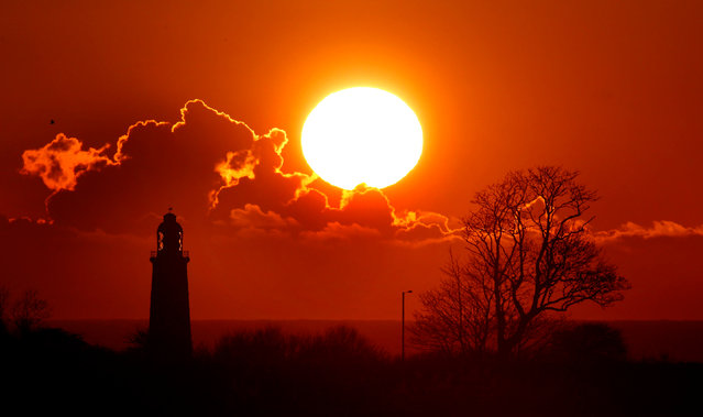 The sun rises beside St Mary's Lighthouse  in Whitley Bay, Tyne and Wear, as the unseasonably cool weather continues on Thursday, April 28, 2016. (Photo by Owen Humphreys/PA Wire)