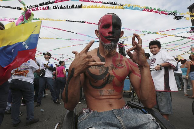 """A man on a wheelchair, painted with the colours of the Sandinista National Liberation Front (FSLN) party flag, takes part in celebrations for the 36th anniversary of the """"Repliegue"""" (Withdrawal) in Managua, Nicaragua July 3, 2015. Thousands of Sandinista supporters marched on Friday in remembrance of the """"Repliegue"""", a tactical military guerrilla offensive that enabled the triumph of the Sandinista Revolution on July 19, 1979. (Photo by Oswaldo Rivas/Reuters)"""