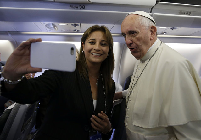 Bolivian journalist Priscilla Quiroga takes a selfie with Pope Francis aboard the papal airplane on its way to Quito, Ecuador, July 5, 2015. The Pontiff is visiting Ecuador, Bolivia and Paraguay during his Apostolic trip from July 5 to July 12. (Photo by Gregorio Borgia/AP Photo)