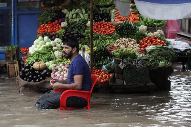 A vendor waits for customers as he sells vegetables amid floodwater, after the rain in Lahore, Pakistan July 16, 2019. (Photo by Mohsin Raza/Reuters)