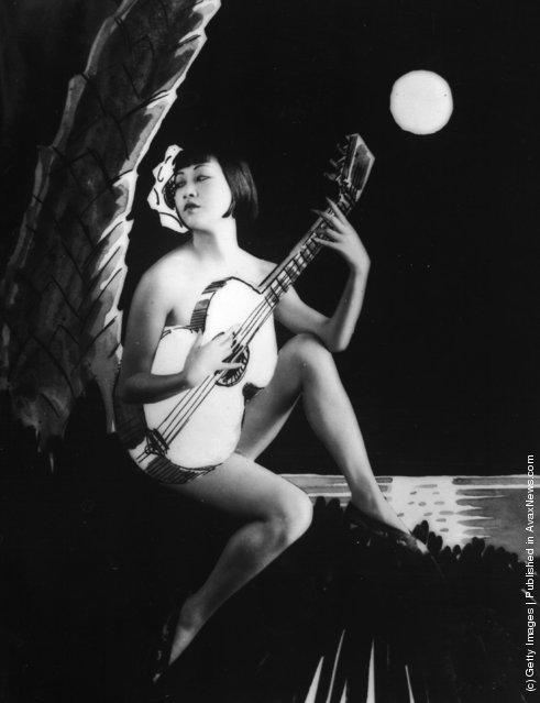 1930: American-Chinese actress Anna May Wong playing a guitar