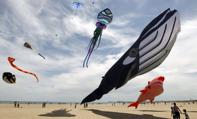 Several kites fly over Malvarrosa beach as part of 17th International Kite Festival in Valencia, eastern Spain, 26 April 2014. Some thousand people take part in the festival running from 25 to 27 April. (Photo by Juan Carlos Cardenas/EPA)