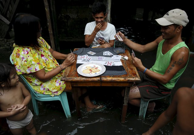 Residents play cards in knee-deep floodwaters at a squatters colony beside a creek in Malhacan, Meycauayan Bulacan north of Manila in the Philippines July 10, 2015. (Photo by Erik De Castro/Reuters)
