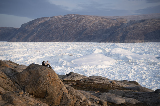 In this August 16, 2019, photo, NYU student researchers sit on top of a rock overlooking the Helheim glacier in Greenland. Summer 2019 is hitting the island hard with record-shattering heat and extreme melt. Scientists estimate that by the end of the summer, about 440 billion tons of ice, maybe more, will have melted or calved off Greenland's giant ice sheet. Helheim glacier has shrunk about 6 miles (10 kilometers) since scientists visited in 2005. (Photo by Felipe Dana/AP Photo)