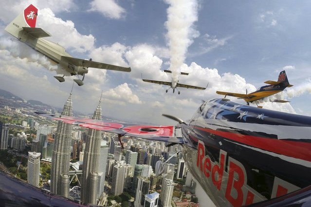 Kirby Chambliss of the United States flies in formation with Matt Hall of Australia, Yoshihide Muroya of Japan and Nigel Lamb of Britain prior to the third stage of the Red Bull Air Race World Championship in front of the Petronas Towers in Kuala Lumpur, Malaysia, on May 15, 2014. (Photo by Joerg Mitter/Red Bull via Reuters)