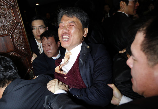 Lawmaker Kim Sun-dong (C) of the Democratic Labour Party struggles with security guards after he detonated a tear gas canister towards the chairman's seat, to try to stop the ruling Grand National Party's move to ratify a bill on a free trade agreement with the U.S., at the National Assembly in Seoul, November 22, 2011. (Photo by Jo Yong-Hak/Reuters)